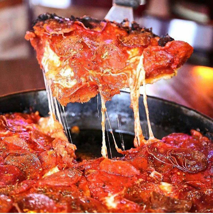 A thick slice of deep-dish pizza as its lifted away from the pie.