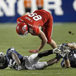 Utah Utes tight end Dallin Rogers (89) jumps past Brigham Young Cougars defensive back Carter Mees (15) and Brigham Young Cougars linebacker Uona Kaveinga (4) as the University of Utah and Brigham Young University play football Saturday, Sept. 17, 2011, in Provo, Utah.