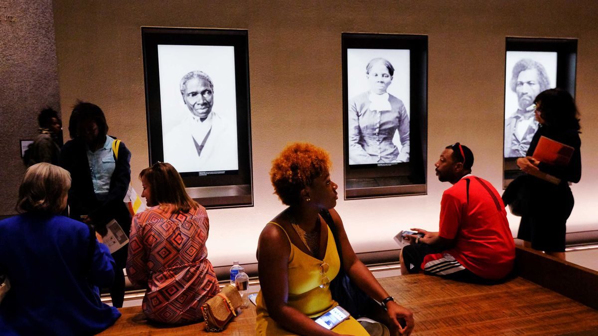 Art gallery patrons sit on a bench in the room where portraits of Sojourner Truth, Harriet Tubman, and Frederick Douglass are displayed.
