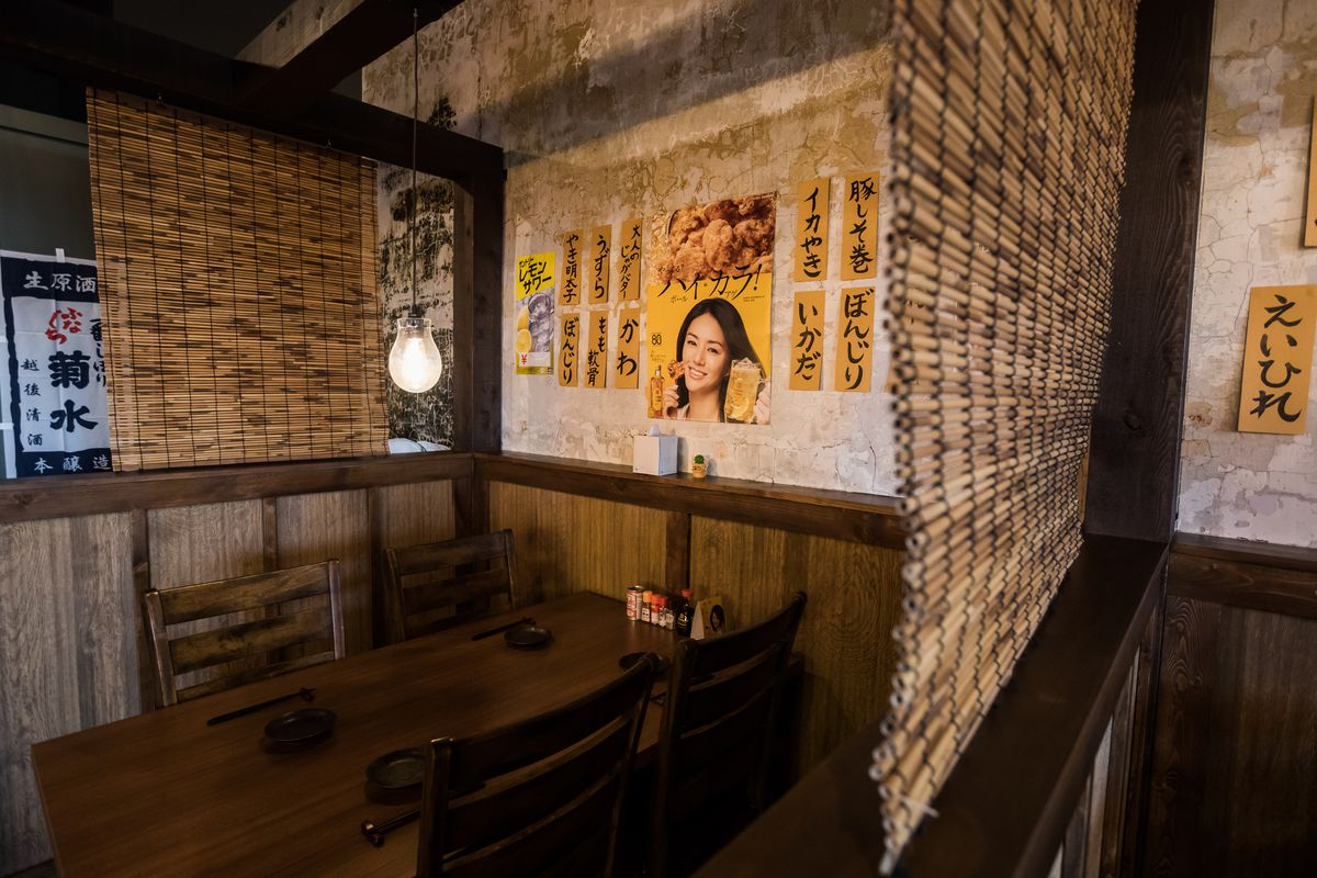 A wooden table surrounded by stylized Japanese posters and bamboo privacy shades.