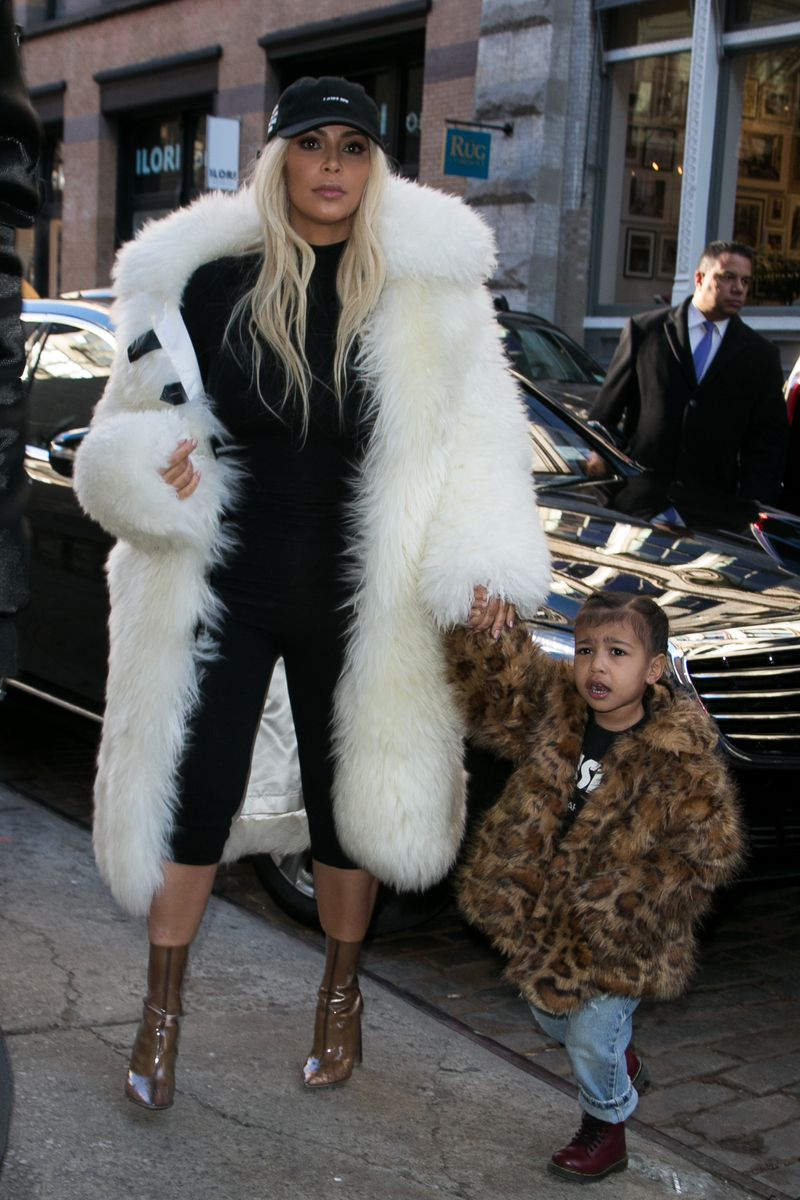 Reality star Kim Kardashian and her young daughter North in fur coats.