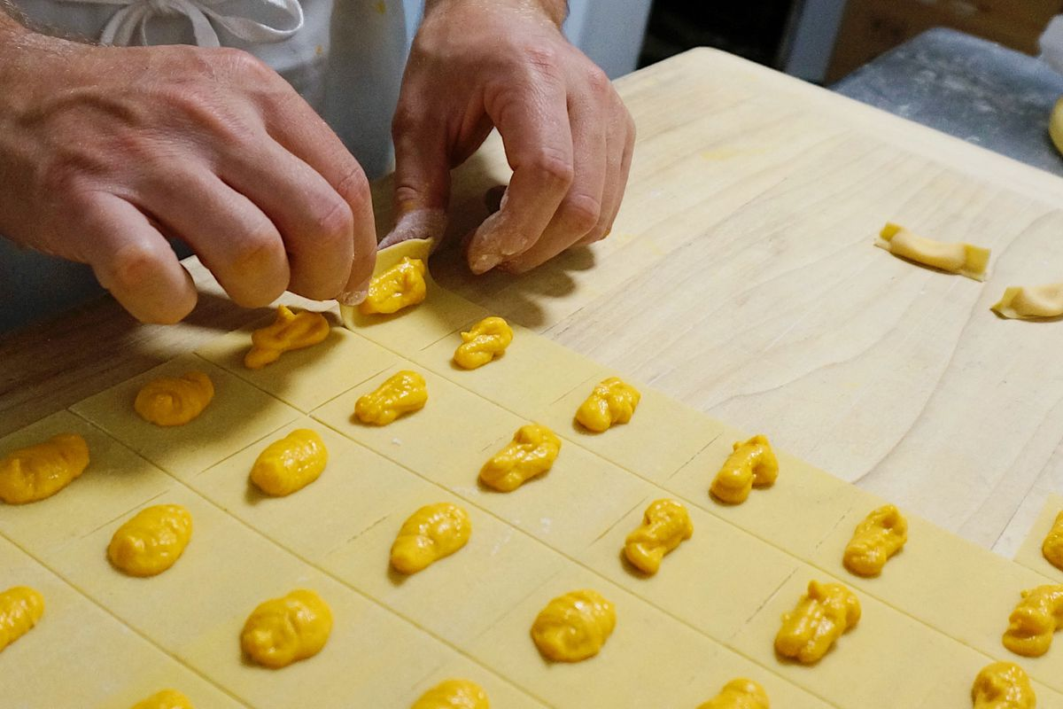 A pair of white hands hovers over a cutting board of pastas, laid out with their fillings but unshapen
