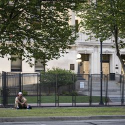 A protester sits by himself near the Kenosha County Courthouse on the 5th night of unrest after police shot Jacob Blake, a markedly quiet night in the city, Thursday night, Aug. 27, 2020.
