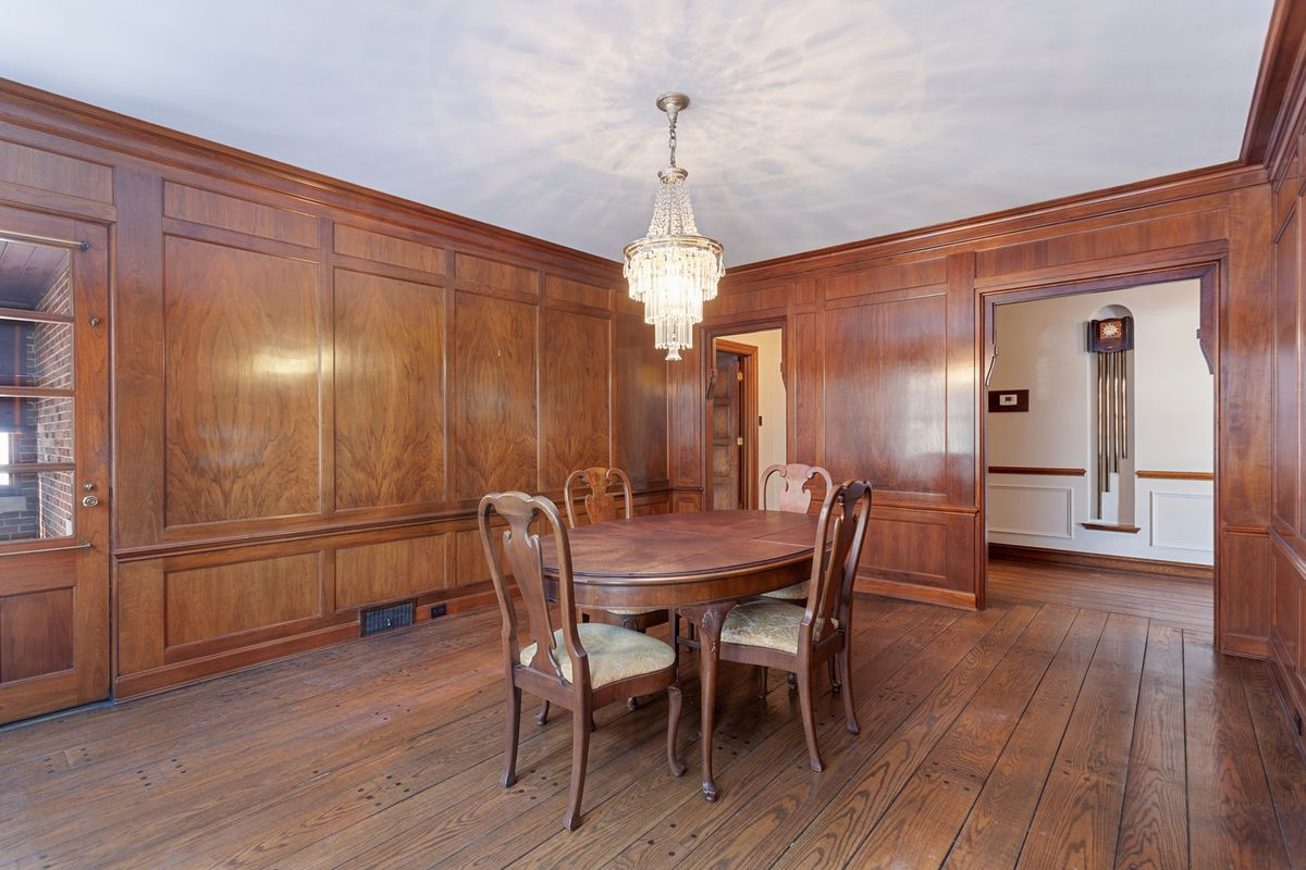 A wood paneled dining room with a chandelier.