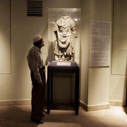 In this Tuesday, Aug. 28, 2012 photo, a worker looks at a damaged statue at the National Museum of Afghanistan in Kabul. Right down to the power cuts that frequently plunge its artifacts into shadow, the National Museum of Afghanistan is a symbol of the country's recent hardships. Its building was shelled, looted and caught fire during the 1992s civil war. Taliban extremists later smashed many centuries- old statues.