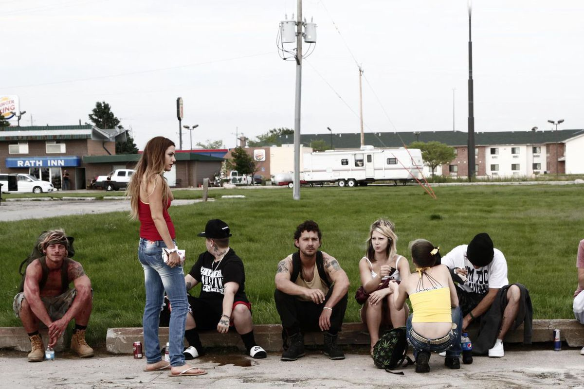 A group of impoverished white youths hanging out in a parking lot.