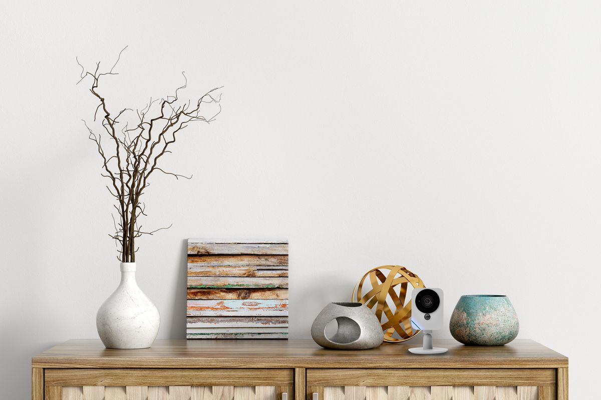 An ADT security camera sits on a wooden entertainment piece inside a home.  A vase with some twigs and other decorative pieces surround it.