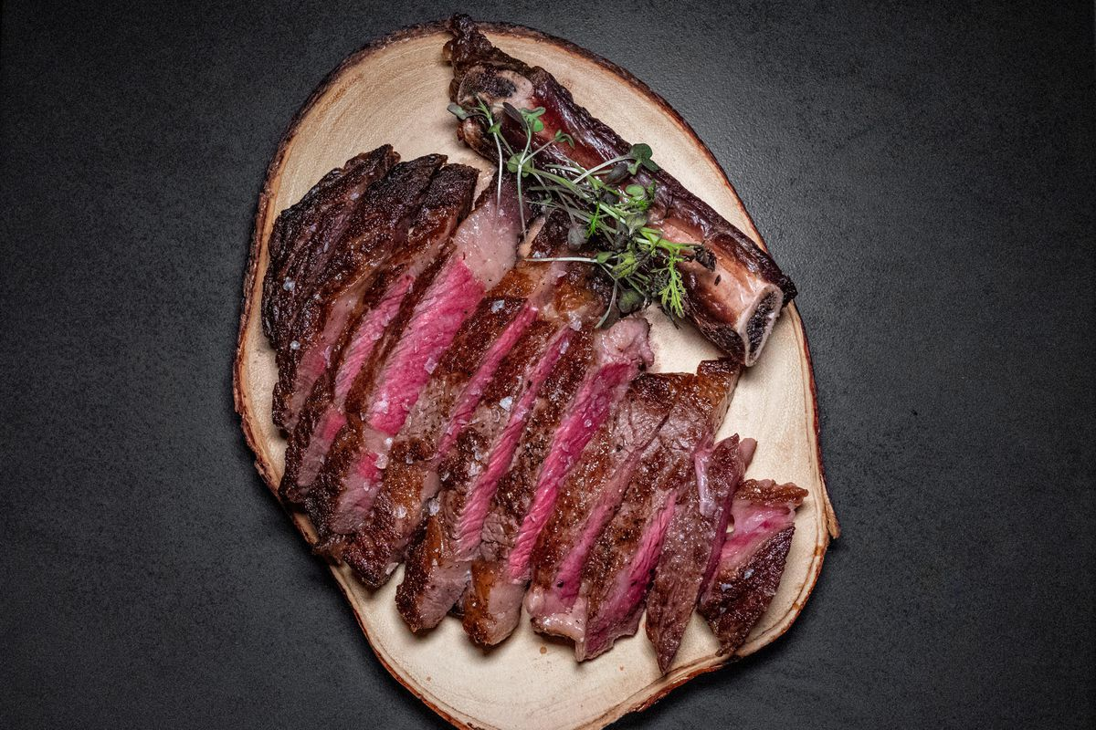 A wagyu ribeye steak, sliced and plated on a wooden board