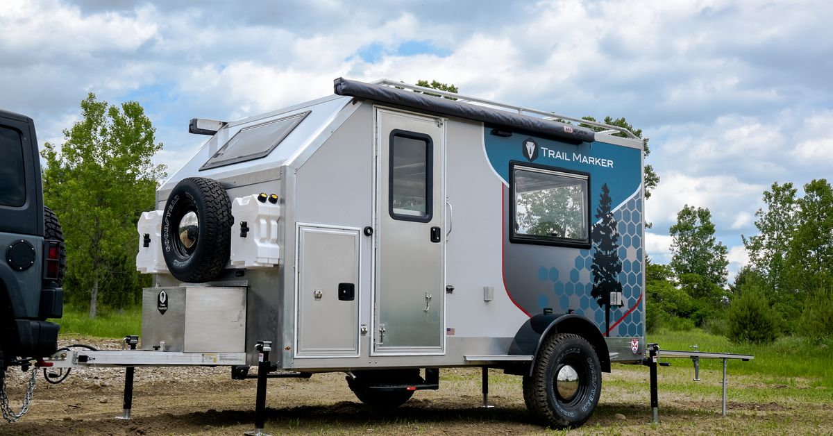 Compact camper trailer uses a drop-down bed to haul gear