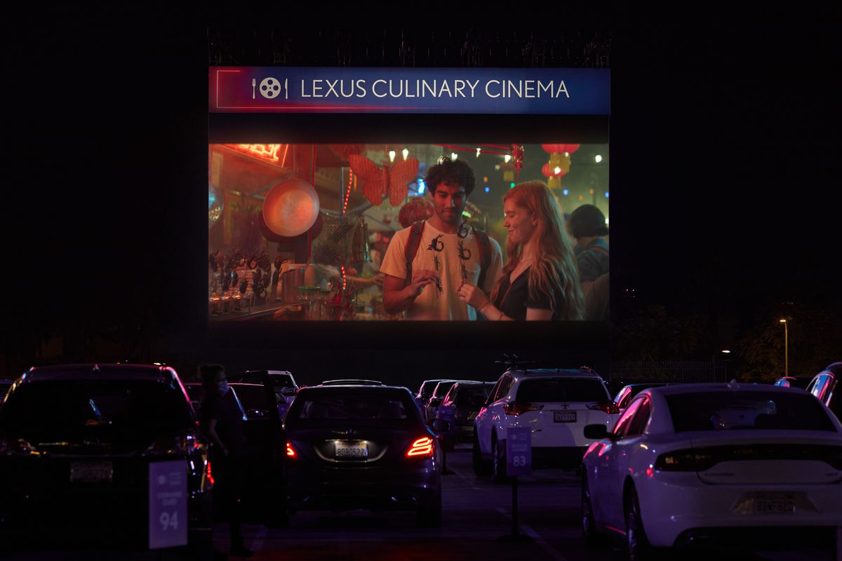 Cars parked in front of a drive-in movie screen at the Lexus Culinary Cinema in Los Angeles. The movie Little Miss Sunshine is playing on the screen, at night.