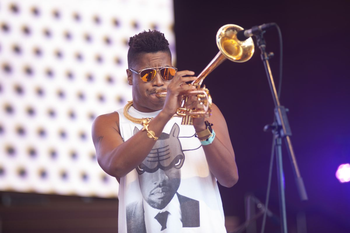 A black man wearing orange tinted sunglasses and a white graphic tank top plays a gold trumpet on stage with a digital screen in the background.