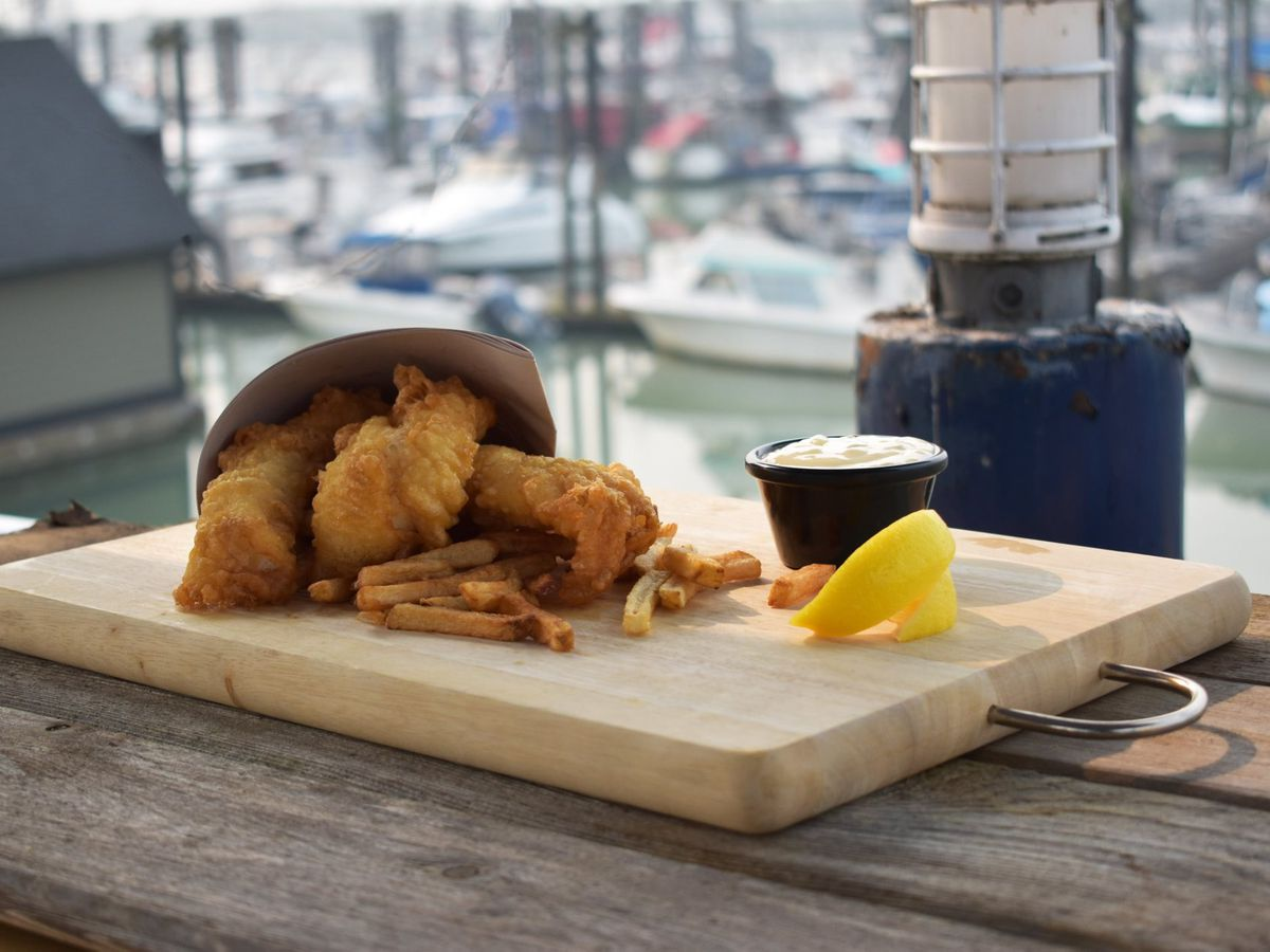 A paper cone overflows fried fish and fries onto a wooden platter beside a small cup of tartar sauce and a slice of lemon, outdoors on a wooden surface with a waterfront in the background
