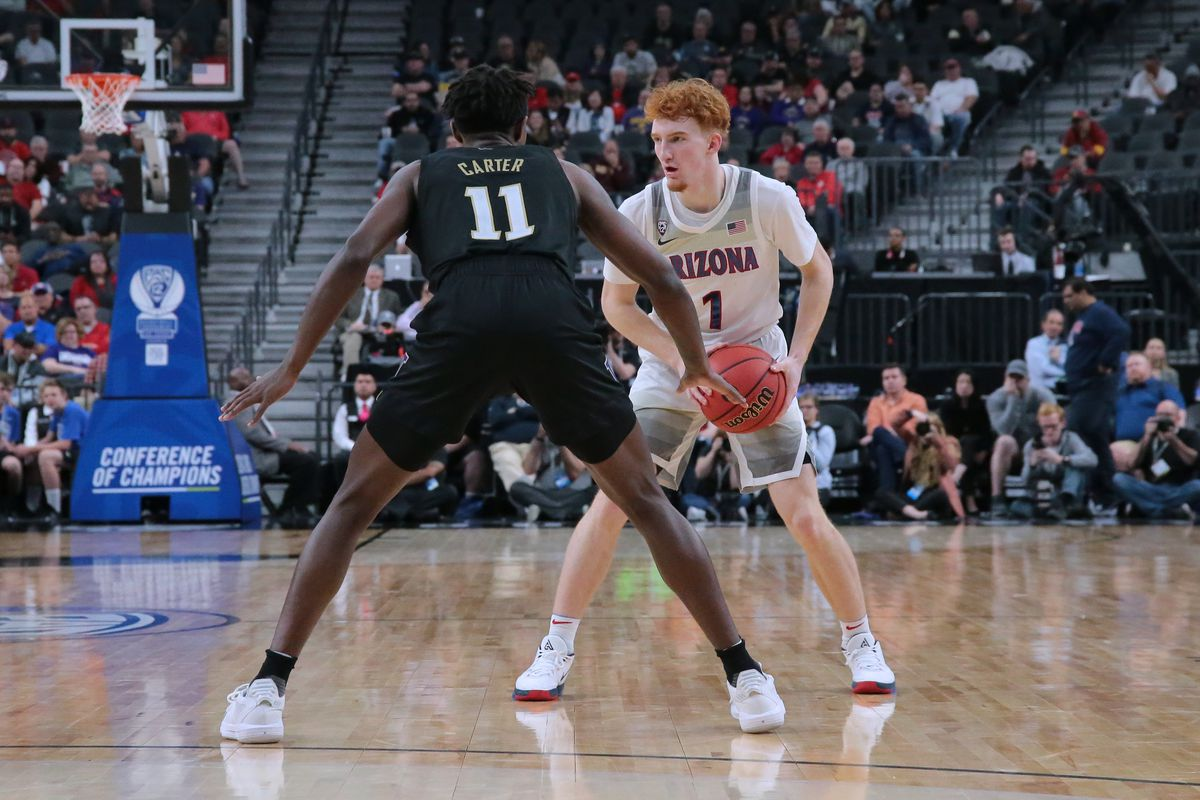 Nico Mannion #1 of the Arizona Wildcats handles the ball against Nahziah Carter #11 of the Washington Huskies during the first round of the Pac-12 Conference basketball tournament at T-Mobile Arena on March 11, 2020 in Las Vegas, Nevada.
