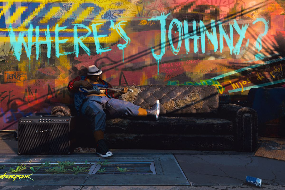 """A man plays guitar on a sofa somewhere in Night City below graffiti that asks """"Where's Johnny?"""" From Cyberpunk 2077, E3 2019."""