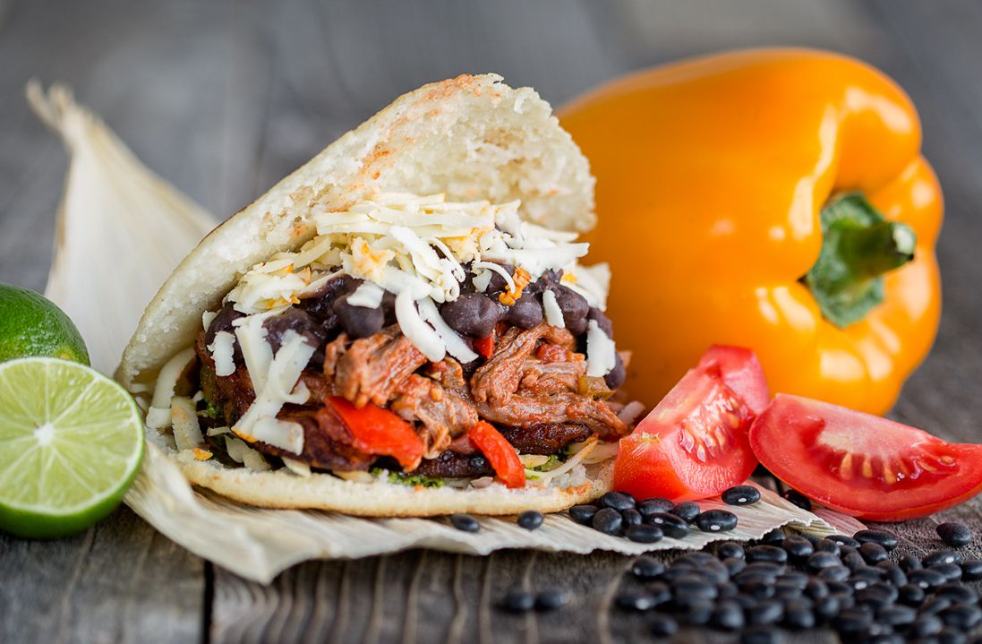 Arepa stuffed with stewed beef, black beans, sweet plantains, cheese, and avocado-cilantrosauce