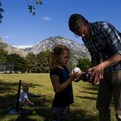 Alex Jensen instructs his daughter Charlotte Jensen, 6, how to use her glove, at Edgemont South Stake Park in Provo on Tuesday, May 30, 2017.