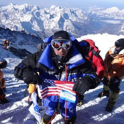 Dave Roskelley stands on the summit of Mount Everest and waves an American flag.