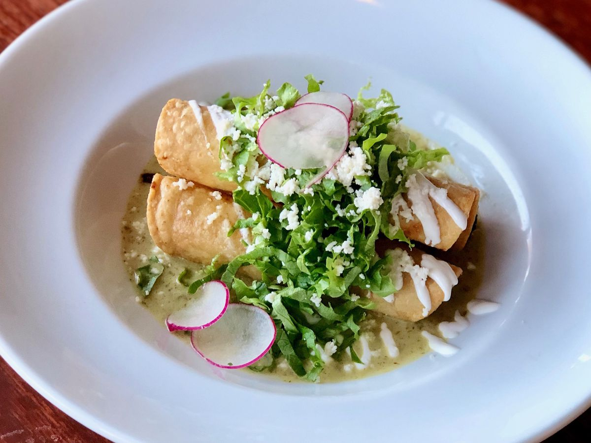 A plate of two flautas with green sauce and sliced radishes.