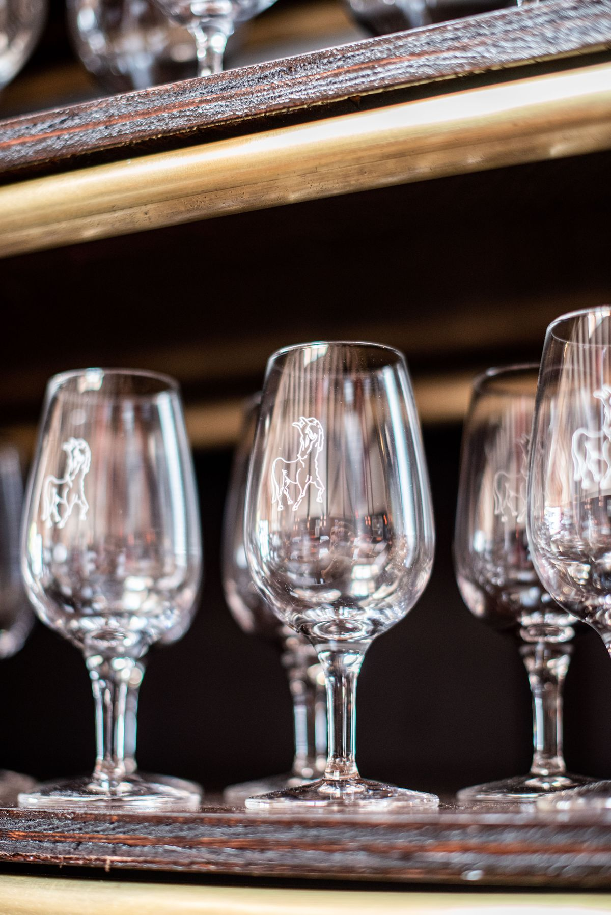 Wine glasses set for service with a notched horse engraved on the outside.