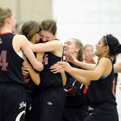 American Fork's Jenna Shepherd (22), second from left, is swarmed by her teammates after hitting the game winner over the Alta Hawks during the state semi-finals at Salt Lake Community College on Friday, Feb. 28, 2014.