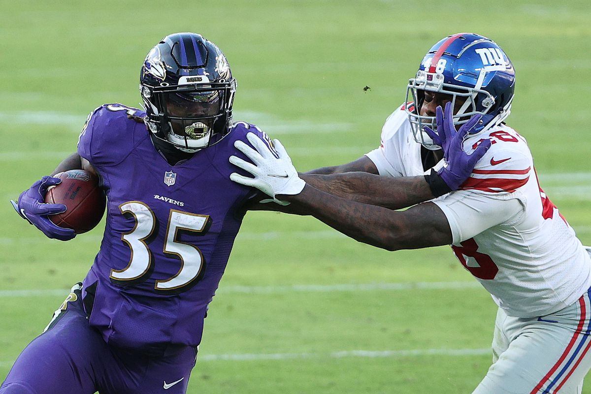 Running back Gus Edwards #35 of the Baltimore Ravens runs against linebacker Tae Crowder #48 of the New York Giants during the second half at M&T Bank Stadium on December 27, 2020 in Baltimore, Maryland.