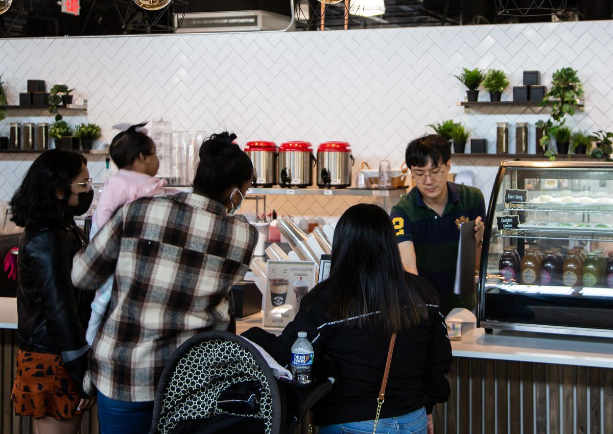 An employee wearing gold wire rim round glasses at Unbelibubble Tea stall at Chattahoochee Food Works gives out an order to a mother with three kids, one of whom is a baby she is holding with a stroller to her right
