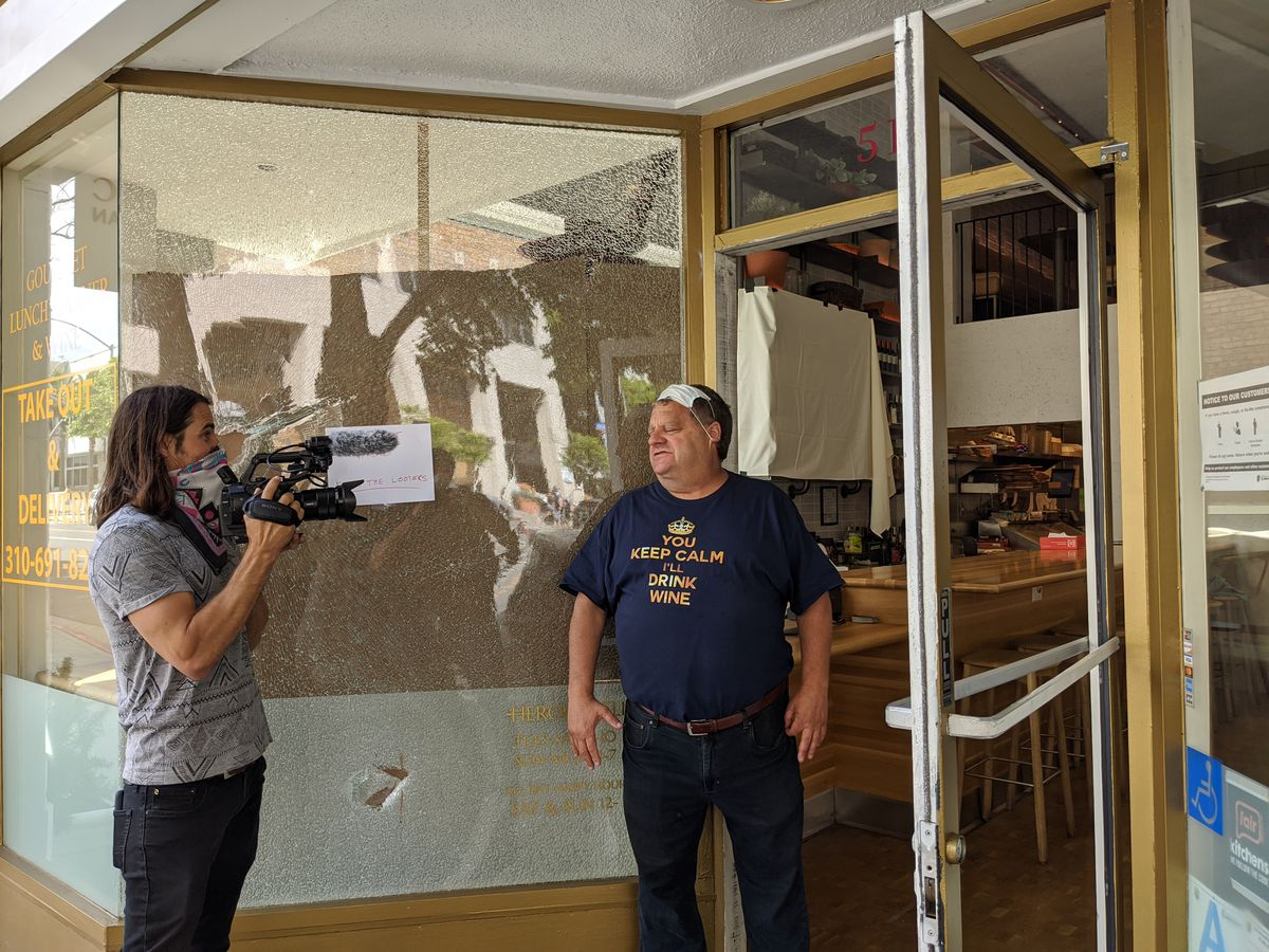 Cameraman interviewing Jeffrey Merrihue, owner of Heroic Italian in Santa Monica, whose windows were broken in the aftermath of the looting.