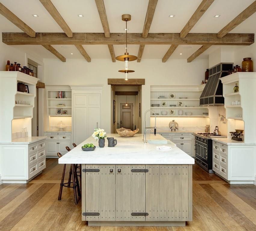 A big, spacious kitchen with a large island in the center and shelves to the side.