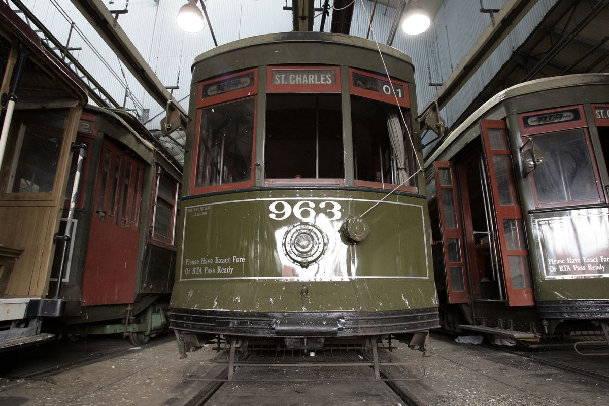 Three green New Orleans streetcars facing forward inside a station.