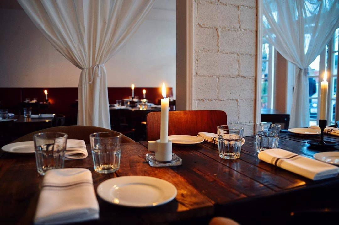 A charming Italian restaurant with wooden table and candle in the middle.