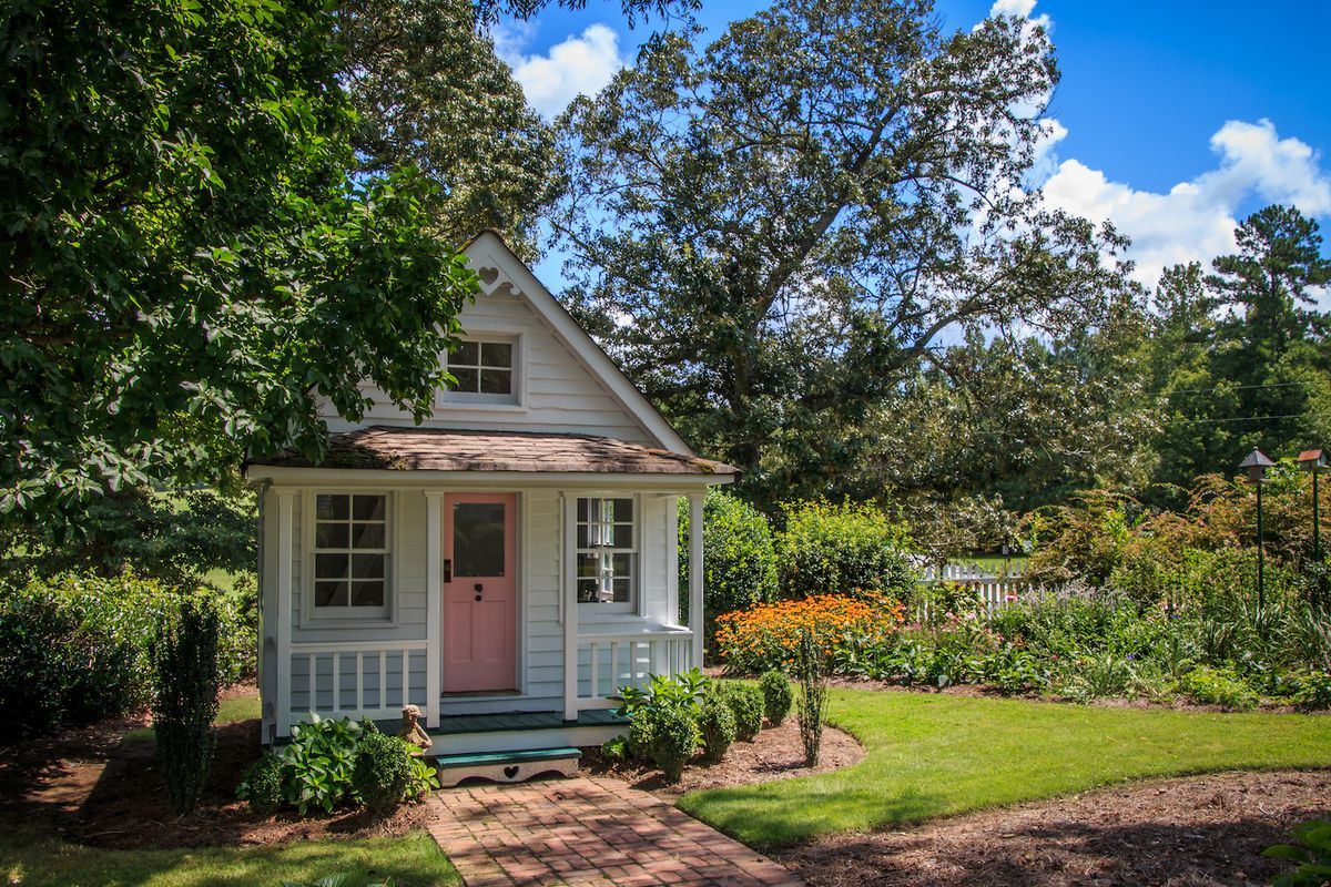 White tiny house with pink door and covered porch.