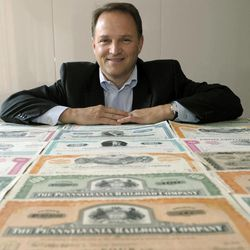 In this Thursday, Sept. 20, 2012, photo, Tom Carroll poses for a portrait with his collection of paper stocks in Washington. At a time when most stock trading is powered by rapid-fire computers, some relish paper stocks for their palpability.
