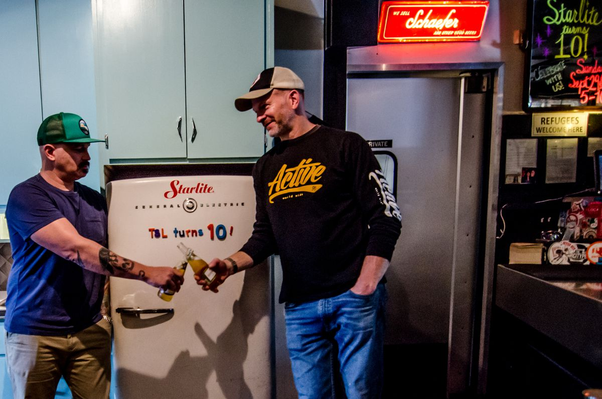 """Two men in casual clothing stand in front of a fridge that reads """"TSL turns 10!"""" in magnets. The men clink bottles of Miller High Life."""