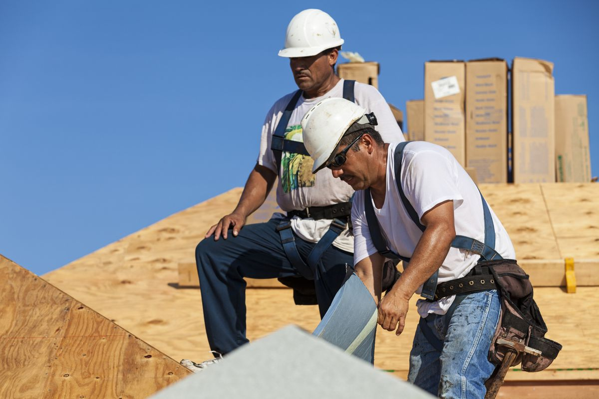 Two Latino workers on a roof.