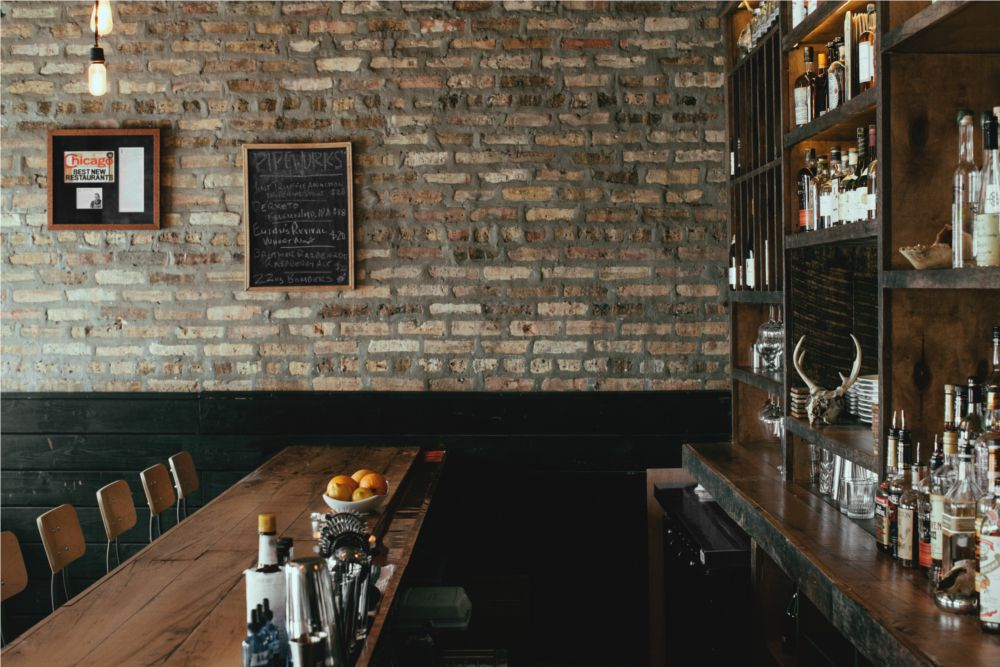 A wooden bar and exposed brick wall