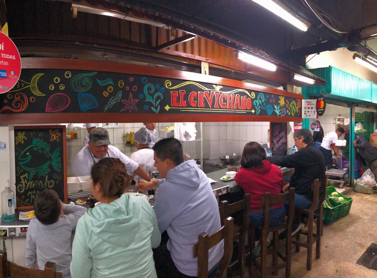 Customers sit at a counter beneath an illustrated sign bearing the name of the El Cevichano stall, while chefs hand diners plates from the kitchen.