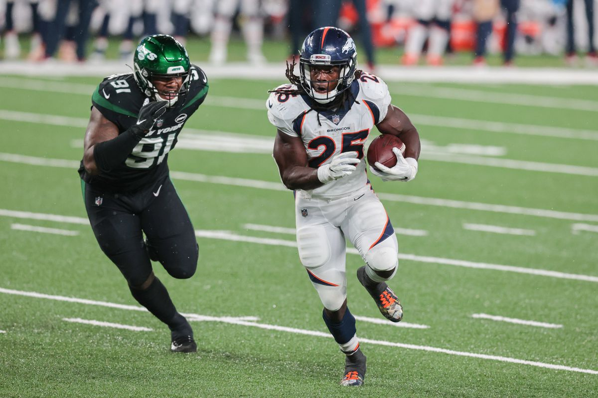 Denver Broncos running back Melvin Gordon carries the ball as New York Jets defensive end John Franklin-Myers pursues during the second half at MetLife Stadium.