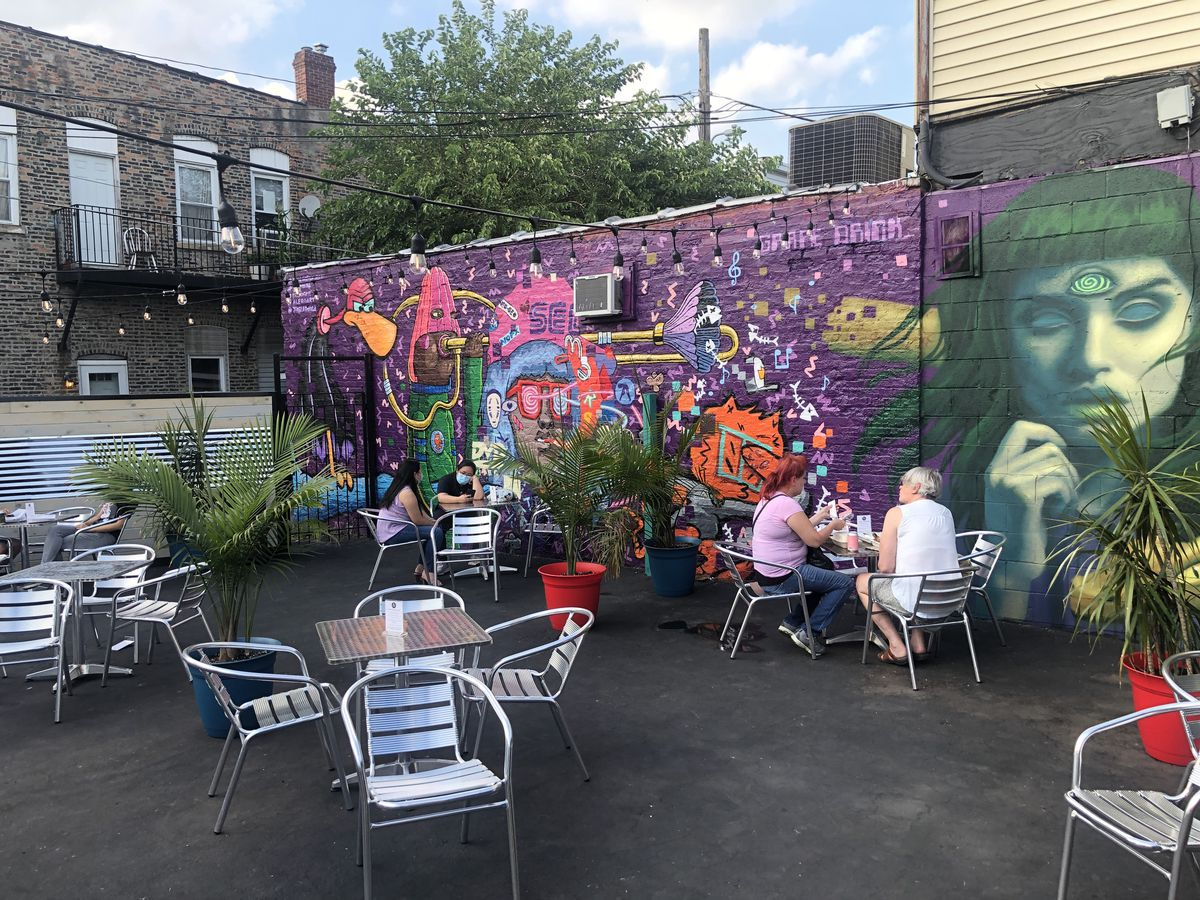 A patio with patio seats and tables, and colorful wall mural with a woman.