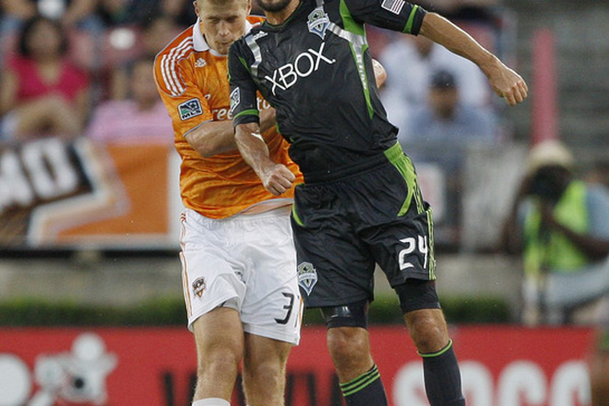 HOUSTON - JULY 30:  Roger Levesque #24 of the Seattle Sounders heads the ball away from Andre Hainult #31 of the Houston Dynamo at Robertson Stadium on July 30, 2011 in Houston, Texas.  (Photo by Bob Levey/Getty Images)