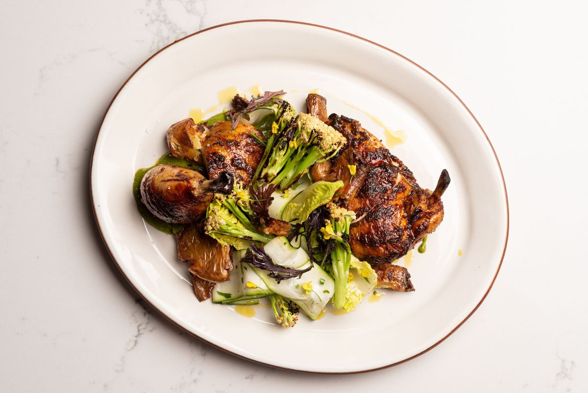 Overhead photo of roasted chicken on an off-white plate with broccoli.