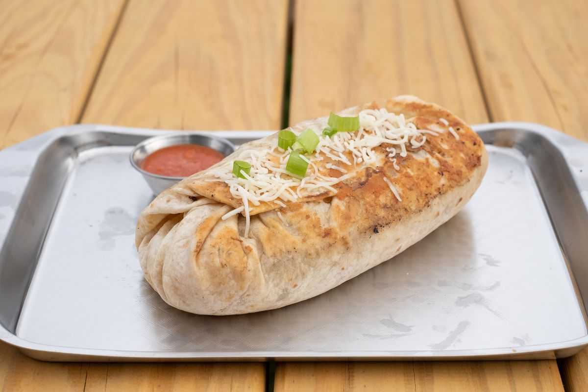 A giant burrito browned crispy on one side, topped with shredded cheese