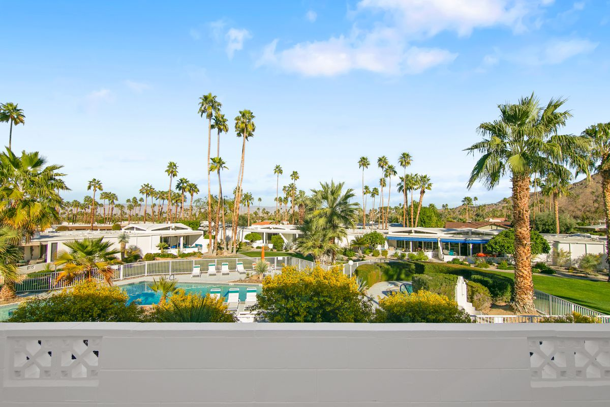 A view of a swimming pool surrounded by grass, palm trees, and white-colored homes.