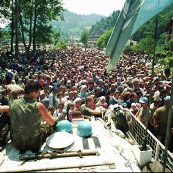 FILE - In this July 13, 1995 file photo, Dutch U.N. peacekeepers sit on top of an armored personnel carrier as Muslim refugees from Srebrenica, eastern Bosnia, gather in the nearby village of Potocari. A Dutch appeals court ruled on Tuesday, June 27, 2017, that the Dutch state is partially liable in the deaths of around 300 Bosnian Muslim men killed by Bosnian Serb army Gen. Ratko Mladic's forces in the 1995 Srebrenica massacre.