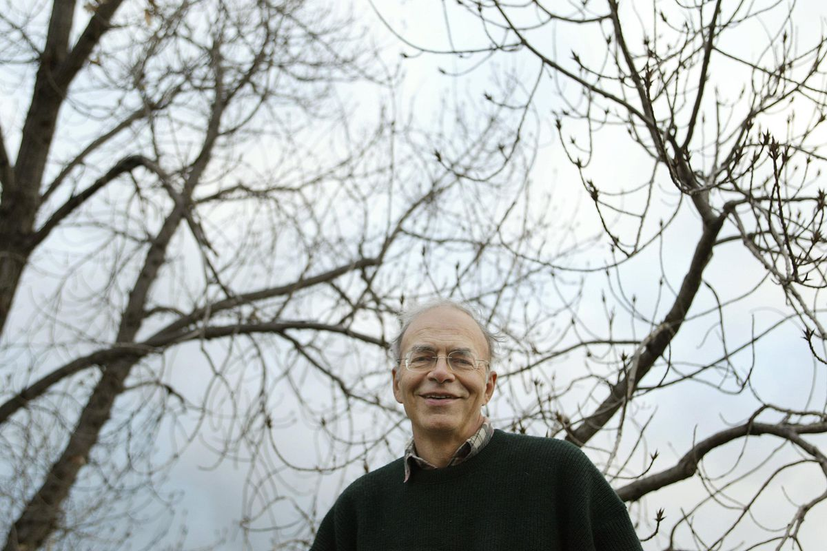 Peter Singer, outdoors with the bare branches of trees behind him.