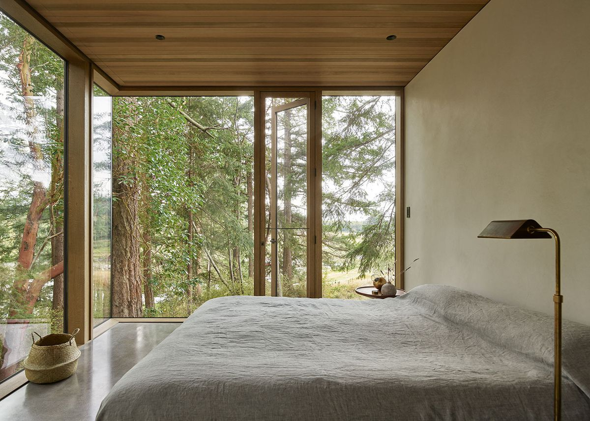 Bedroom featuring large windows and neutral colors.