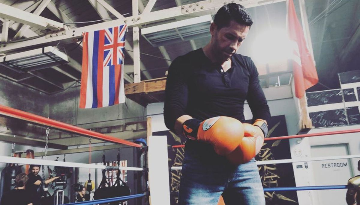 Scott Adkins stands in a boxing ring, wearing jeans and a tight polo shirt, looking down at his big orange boxing gloves.