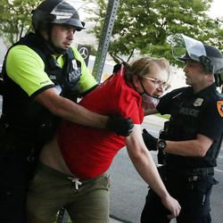 A protester is detained by Salt Lake City police officers for failing to disperse after a protest at the district attorney's office in Salt Lake City on Thursday, July 9, 2020. Protesters gathered on Thursday night outside the building in response to Salt Lake County District Attorney Sim Gill's ruling earlier in the day that the police killing of Bernardo Palacios-Carbajal was legally justified.