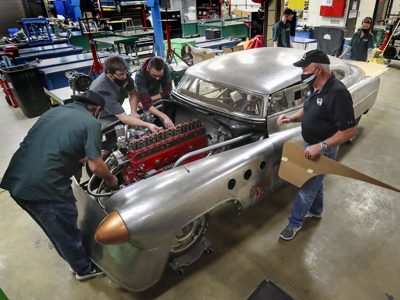 """Jeff Holm, UVU Transportation Technology professional in residence, right, and Todd Low, UVU race team director, second from left, work with UVU automotive students Jordan Olsen, left, Anderson Workman, James Spackman and Hadley Tibbitts, right, as they work on """"Bombshell Betty,"""" the iconic 1952 Buick that broke six land speed world records at the Bonneville Speedway in Utah, at the Sparks Automotive building on the UVU campus in Orem on Wednesday, Nov. 18, 2020. The team has updated and reengineered the vehicle to break the 200 mph mark."""