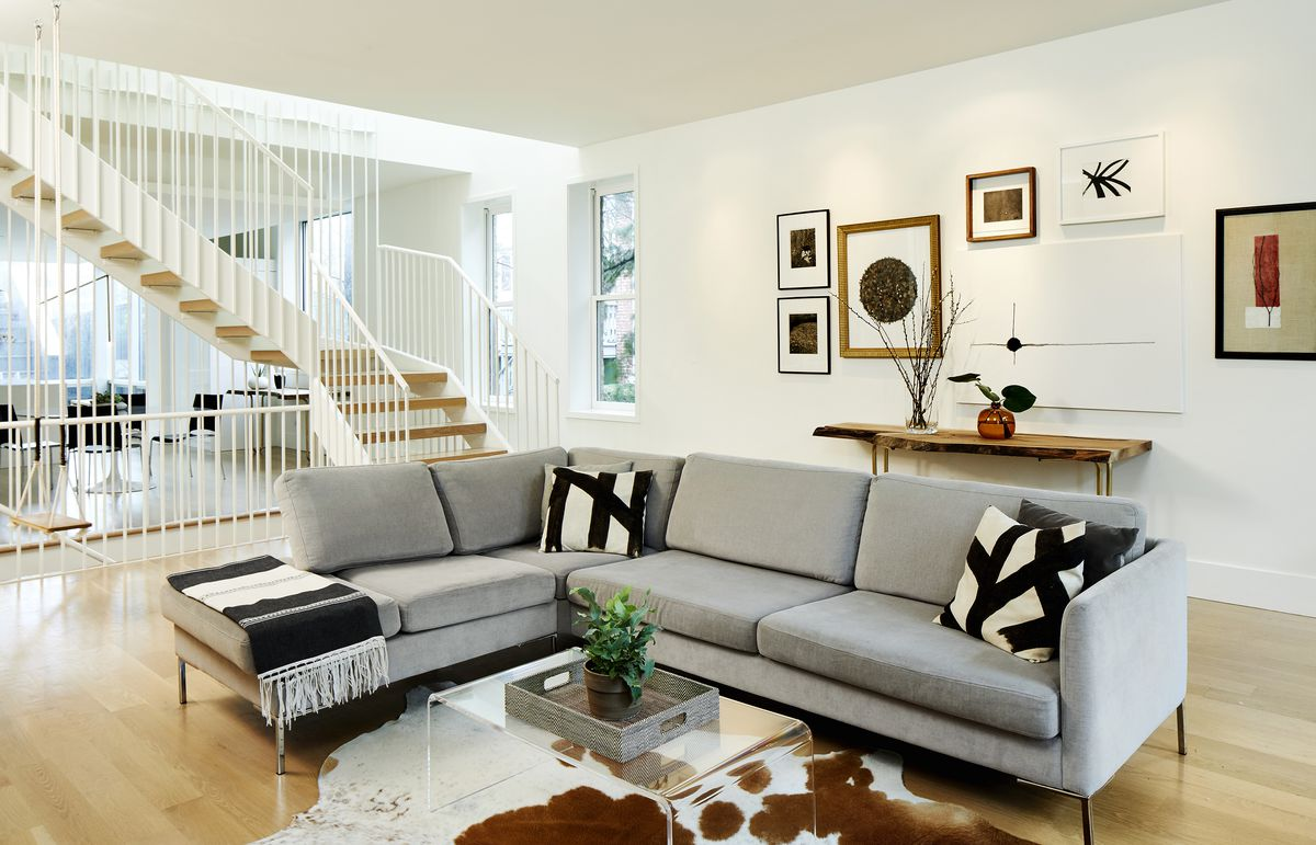 A living room is sparsely furnished with a sectional sofa, a lucite coffee table, and console.