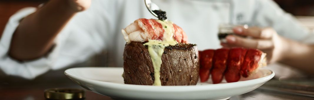A hand holds a spoon, placing a dollop of caviar on top of lobster on top of a steak at Fleming's